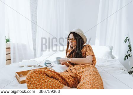 Beautiful Young Stylish Woman In Glasses And White Hat Lying On Bed And Drinking Coffee In Sunny Mor