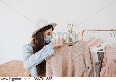 Stylish Caucasian Young Woman In Protective Mask And Business Suit In Fashion Boutique While Shoppin