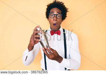 Handsome african american bartender man with afro hair preparing cocktail mixing drink with shaker afraid and shocked with surprise and amazed expression, fear and excited face.