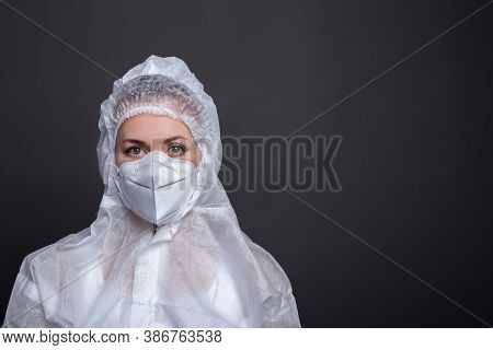 Portrait Of Young Female Doctor In A Protective Mask On A Gray Backgound. Medic In Protective Clothi