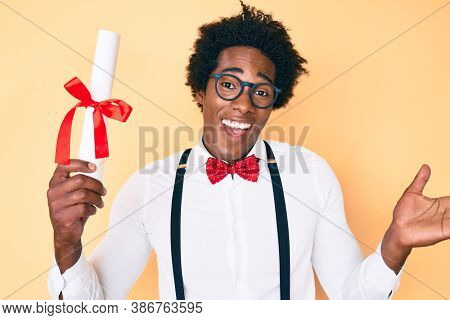 Handsome african american nerd man with afro hair holding graduate degree diploma celebrating achievement with happy smile and winner expression with raised hand