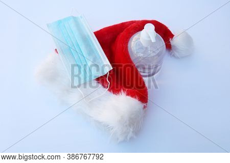 Naughty Santa Claus Hat with Face Mask. Covid-19 Christmas. Coronavirus Face Mask with Santa Hat and Hand Sanitizer. Coronavirus is dangerous be safe.