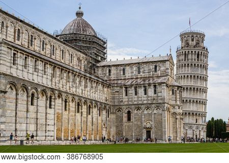 Pisa, Italy - July 9, 2017: View Of Tourists, Pisa Cathedral And Leaning Tower In Piazza Dei Miracol