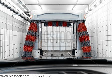 Inside Vehicle Pov Automatic Modern Brush Carwash Station Facility With Soft Red Grey Brushes, Wax A