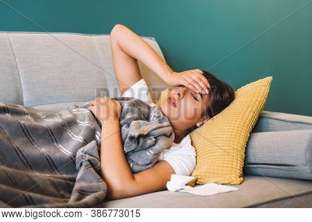 Tired Young Female Touching Forehead Having Headache Migraine Or Fever, Lying On A Sofa In Living Ro