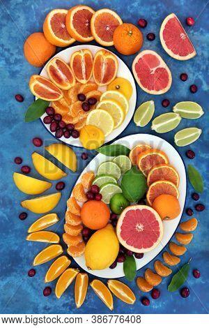 Summer sunshine citrus fruit with oranges, lemons, limes, grapefruit & cranberries high in antioxidants, anthocyanins, lycopene, fibre & vitamin c. Immune boosting healthcare concept. On mottled blue.