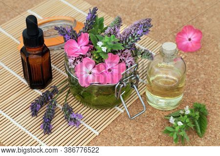 Naturopathic herbal medicine with summer flowers and herbs loose and steeping in a jar with oils to make aromatherapy essential oil. Still life on bamboo and cork. Natural health care concept.
