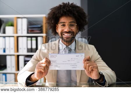 Holding Paycheck Or Payroll Check. Insurance Cheque In Hand
