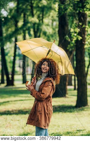 Curly Woman In Raincoat Holding Umbrella And Looking At Camera In Park
