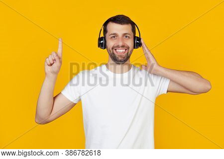 Young Man With A Beard In A White T-shirt Listens To Music With Headphones Over Isolated Yellow Back