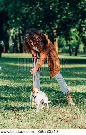 Selective Focus Of Curly Woman In Raincoat Playing With Jack Russell Terrier In Park