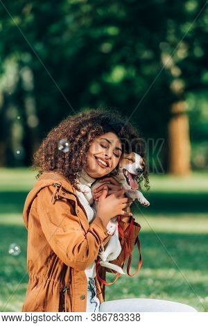 Selective Focus Of Woman In Raincoat Embracing Jack Russell Terrier Near Soap Bubbles In Park