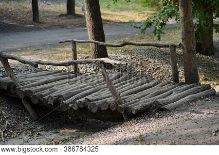 Close Up Of Old Wooden Bridge In Forest Park. Decrepit Footbridge From Wood In Countryside