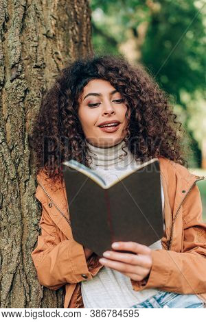 Selective Focus Of Brunette Woman In Raincoat Looking At Notebook Beside Tree In Park