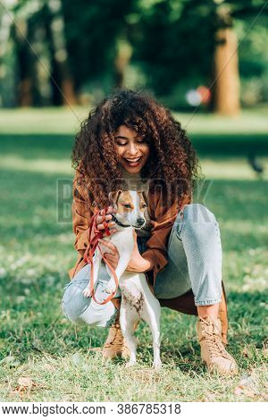 Selective Focus Of Woman In Raincoat Petting Jack Russell Terrier In Park