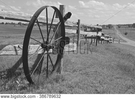 An Old Spoked Wagon Wheel, Rests Along A Weathered Wooden Fenceline Out In The Countryside. (black A