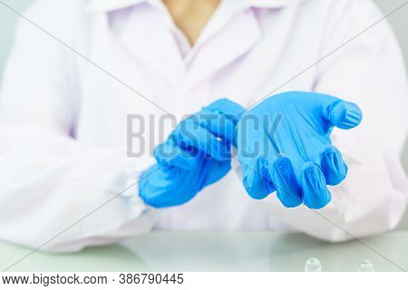 Scientist Hands Putting In Nitrile Blue Latex Gloves In Labcoat Wearing Nitrile Gloves