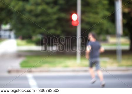 Blurred Background. A Man Runs Across The Street At A Red Traffic Light. After The Signal Turns Red,