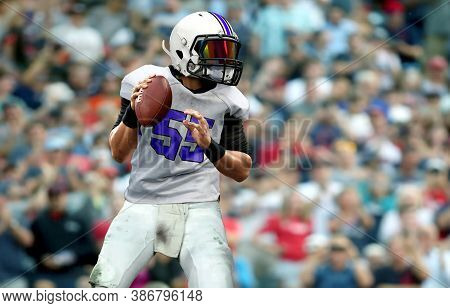 American Football Quarterback  Getting Ready To Throw A Ball With Spectator In Background