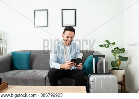 Handsome Young Man Using An App To Get A Taxi While Sitting In His Living Room Couch Next To A Suitc