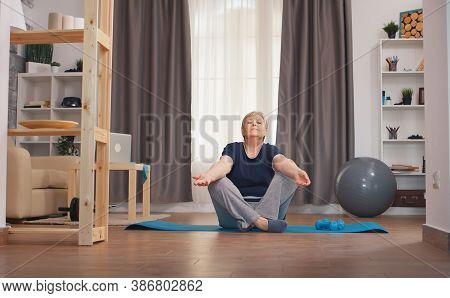 Senior Woman Relaxing In Living Room Doing Yoga. Active Healthy Lifestyle Sporty Old Person Training