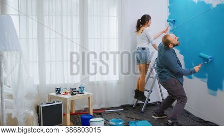 Cheerful Couple Painting And Dancing While Redecorating Living Room. Happy Family. Apartment Redecor