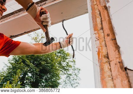 A Worker Dismantles An Old Window In The House With A Crowbar.