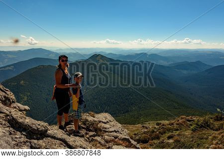 Family On One Of The Peaks Of The Ukrainian Carpathians, Parents And Children Admire The Views Of Th