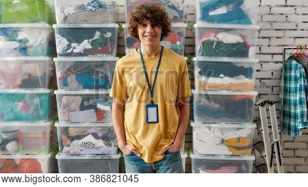 Caucasian Guy Smiling At Camera, Posing In Front Of Rack And Boxes Full Of Clothes, Young Volunteer