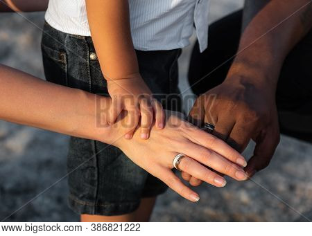 Close Up Of Three Multiracial Family Person Stack Their Palms. Multi Racial Love And Integration Bet