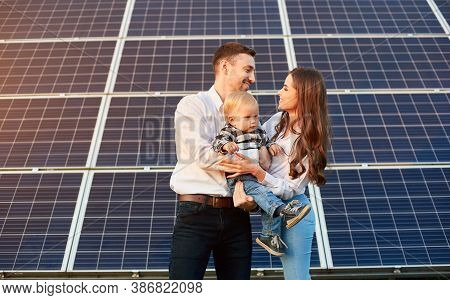 Young Family With A Small Child In Her Arms On A Background Of Solar Panels. A Man And A Woman Look