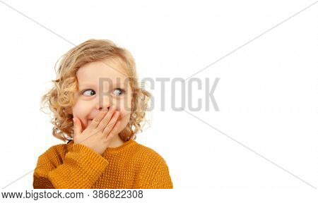 Shy funny child covering his mouth isolated on a white background