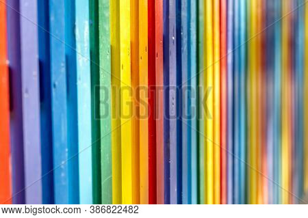 Part Of Wooden, Rainbow Colorful Painted Fence  On A Sunny Hot Summer Day In A City Park. Abstract M