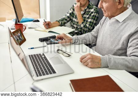 Cropped Shot Of Aged Man, Senior Intern Checking Time On The Cell Phone While Sitting At Desk, Worki