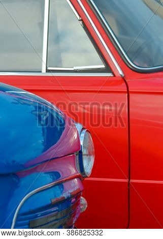 Headlight Of A Blue Vintage Car On The Background Of A Red Car