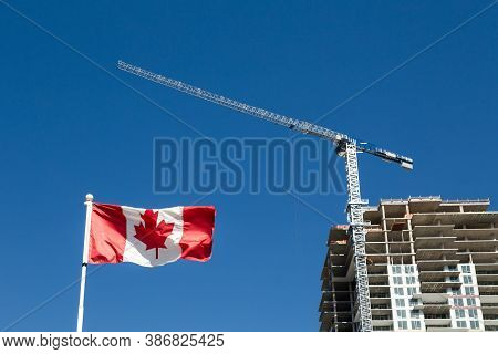Canadian Flag With Apartment Building Under Construction In The Background, Canadian Economy And Hou