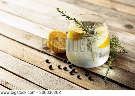 Alcohol Drink (gin Tonic Cocktail) With Lemon, Juniper Branch,  And Ice On Rustic Wooden Table, Copy