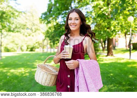 leisure and people concept - happy smiling woman with picnic basket, coffee cup and blanket at summer park