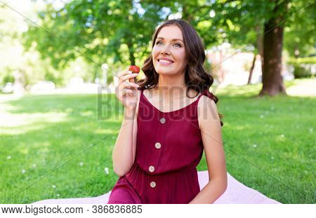 leisure and people concept - happy smiling woman eating strawberry sitting on picnic blanket at summer park