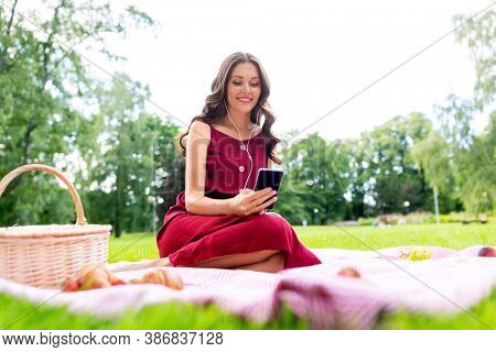 leisure and people concept - happy smiling woman with smartphone and earphones, picnic basket and food sitting on blanket at summer park and listening to music