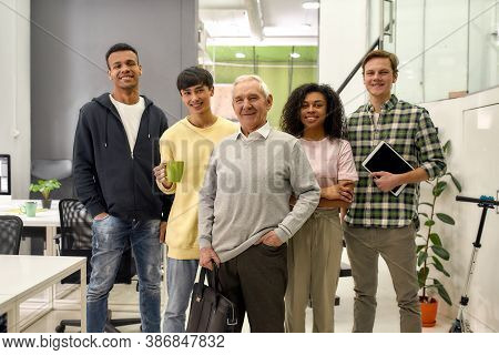 Happy Diverse Team Of Employees Looking At Camera While Posing With Senior Intern, Standing Together