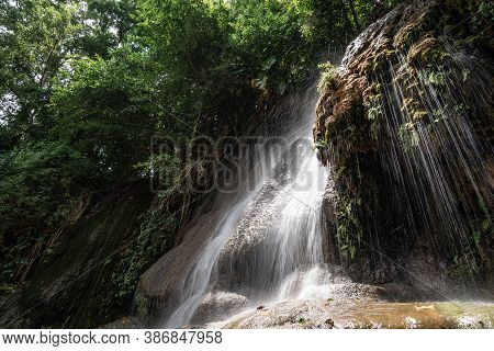 Waterfall In Tropical Rainforest With Rock And Sunlight. Saiyok Noi Waterfall, Located In Kanchanabu