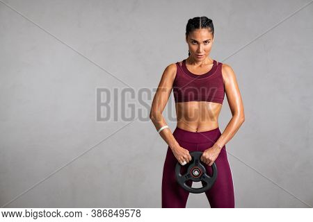 Portrait of beautiful fit woman exercising with a weight plate. Determined sportswoman lifting heavy weight dumbbell isolated on gray background.