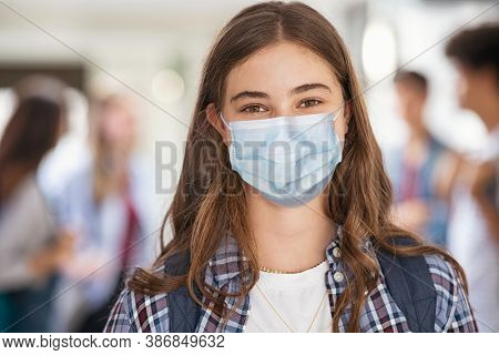 Portrait of girl wearing a face mask standing in college campus and looking at camera. University young woman smiling despite the Covid-19 pandemic. Satisfied and proud student girl with surgical mask