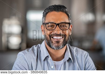 Smiling mature indian man wearing spectacles and looking at camera. Middle eastern confident businessman at office. Portrait of successful mid entrepreneur feeling satisfied and working from home.