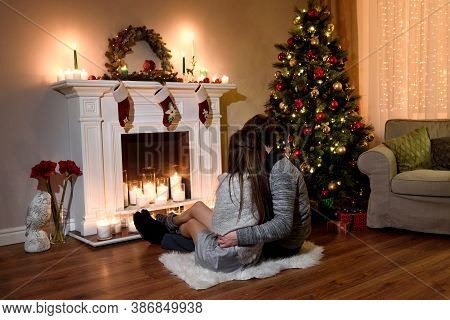 Young Couple In Love Sitting By The Fireplace Decorated Or Christmas And Looking At Fire. A Cozy Eve