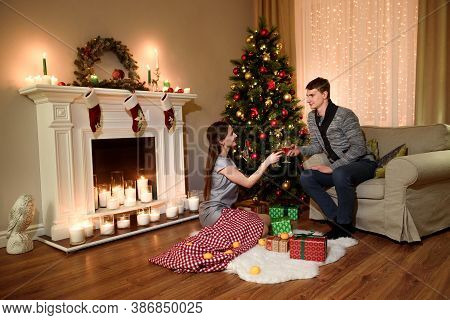 Happy Couple Having Drinks By A Fireplace In A Cozy Dark Living Room On Christmas Eve. Happy Young P