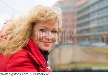 Portrait of a blonde woman on a bridge railing
