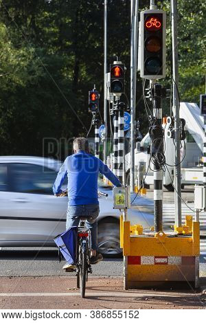 Cyclist Waiting For Red Light Of A Temporary Traffic Light Because Of Roadworks In Rotterdam In The