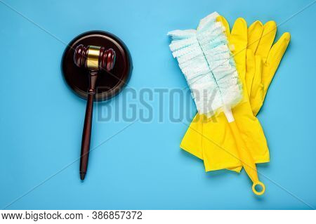 .rubber Gloves And Mallet On A Blue Background. Concept Of Litigation At A Cleaning Company.